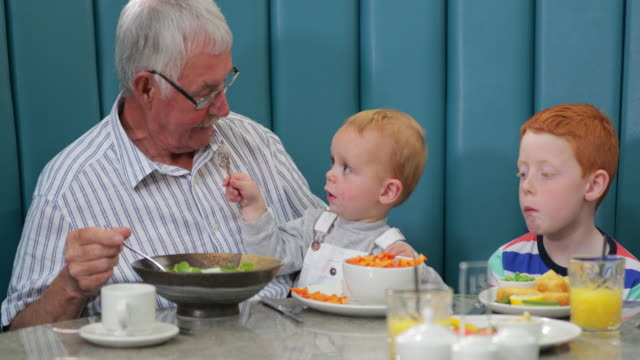 grandfather in a restaurant with his young grandsons - reaching stock videos & royalty-free footage