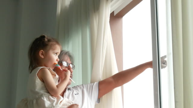 grandfather is carrying niece , pointing for looking scene out of window - lollipop stock videos & royalty-free footage