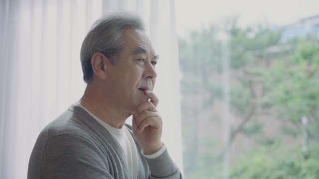 a grandfather is deep in thought looking out the window at home - korean ethnicity stock videos & royalty-free footage