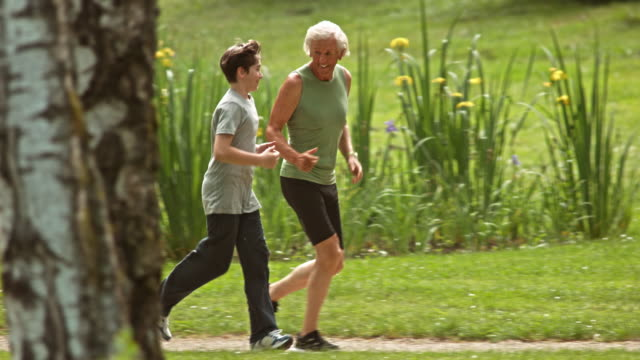 slo mo ts grandfather jogging in the park with his grandson - vest stock videos & royalty-free footage