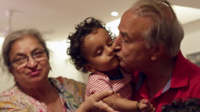 Grandfather kisses both his twin grand sons whjile grandmother is looking at them