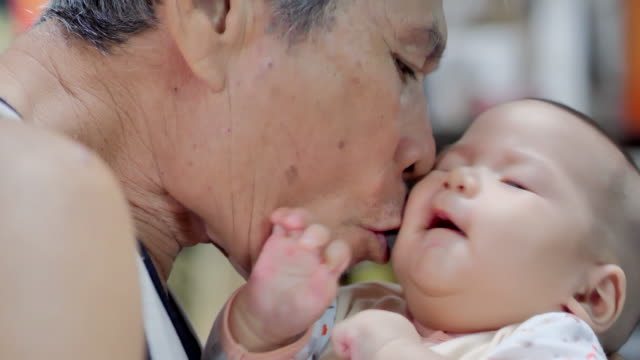 grandfather kissing grandson at home.relaxing and comforting on the shoulder of her grandparents.family relationship between grandfather and grandson.asian family,life insurance concept.relations and people concept.video brief: a grandparents love - grandchild stock videos & royalty-free footage