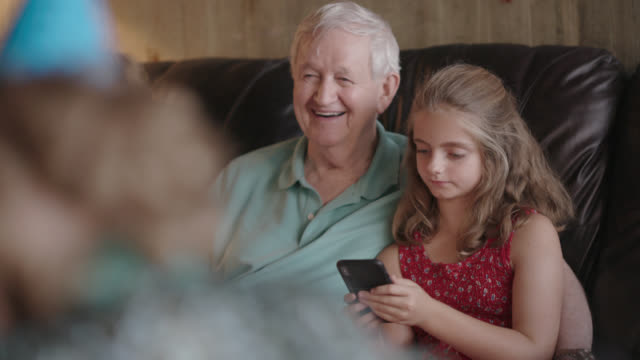 grandfather laughs while looking at his granddaughter's phone as they together on a living room couch - großvater stock-videos und b-roll-filmmaterial