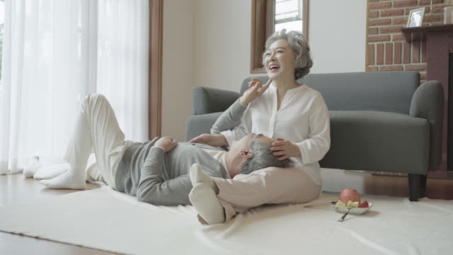 a grandfather lies to play with a grandmother in living room at home - 韓国人点の映像素材/bロール