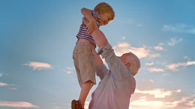 slo mo grandfather lifting his grandson into the air in sunshine - grandchild stock videos & royalty-free footage