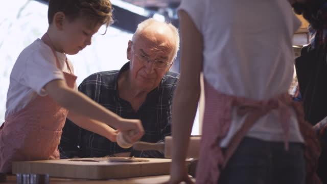 Grandfather looking at playful grandchildren making cookies