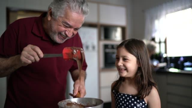 großvater macht schokolade mit enkelin zu hause - 65 69 jahre stock-videos und b-roll-filmmaterial