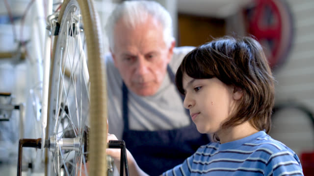 grandfather motivating and teaching his grandson to fix a bicycle at their family business - grandchild stock videos & royalty-free footage
