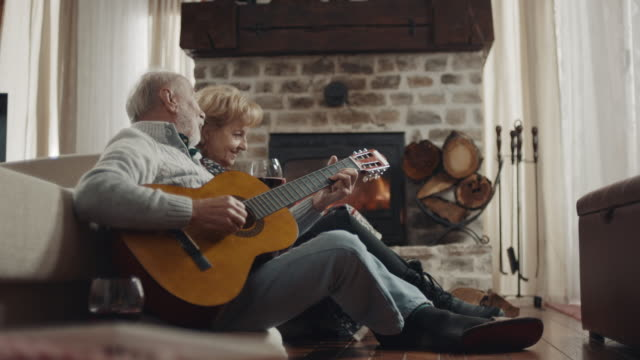 grandfather playing guitar to grandmother and grandson - log stock videos & royalty-free footage