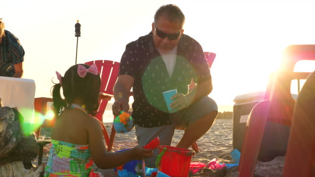 ms grandfather playing in sand with young granddaughter during family beach party - kneeling stock videos & royalty-free footage