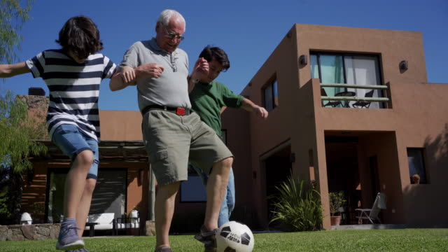 grandfather playing soccer with grandsons in the back yard - grandparent stock videos & royalty-free footage