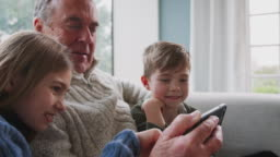 Grandfather Playing Video Game With Grandchildren On Mobile Phone At Home