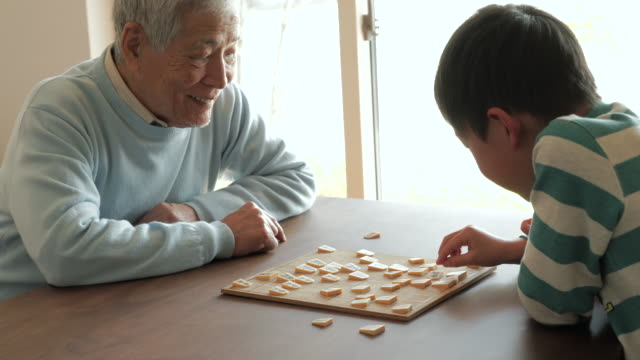 grandfather playing with a japanese chess with grandson at home - japanese ethnicity stock videos & royalty-free footage