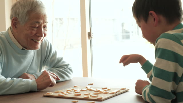 grandfather playing with a japanese chess with grandson at home - grandfather stock videos & royalty-free footage