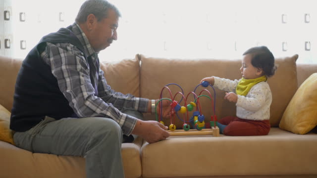grandfather playing with little grandson sitting on sofa, plays with a bead roller coaster - turchia video stock e b–roll