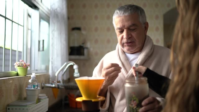 grandfather preparing coffee with her granddaughter at home - routine stock videos & royalty-free footage