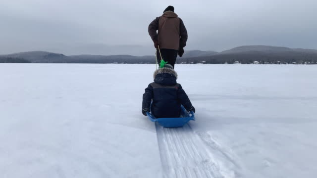 grandfather pulling grandson on sled on frozen lake in winter - pulling stock videos & royalty-free footage