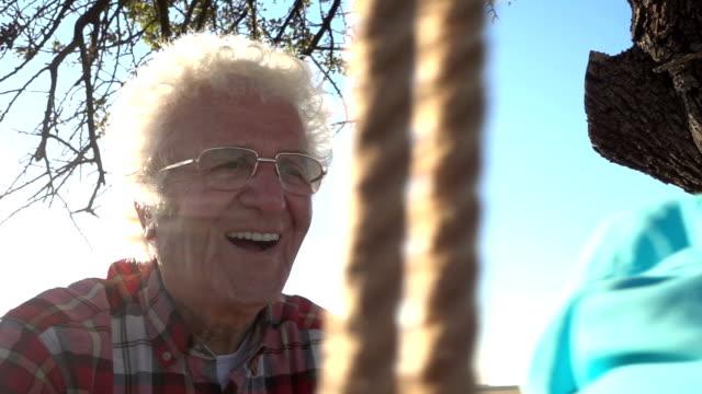 Großvater schiebt glücklich Enkel auf Schaukel