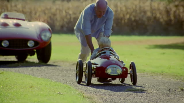 grandfather pushing grandson in toy car on gravel pathway - großvater stock-videos und b-roll-filmmaterial