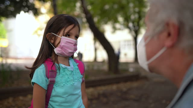 grandfather putting protective face mask to his granddaughter at school yard - rucksack stock videos & royalty-free footage