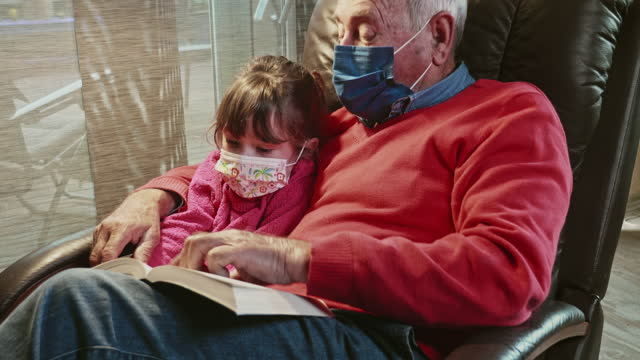 grandfather reading a book to his granddaughter during the pandemic - granddaughter stock videos & royalty-free footage