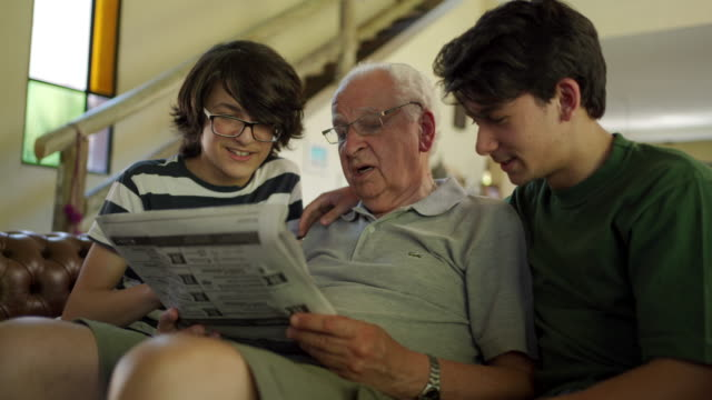 vídeos de stock e filmes b-roll de grandfather reading newspaper with grandsons - jornal