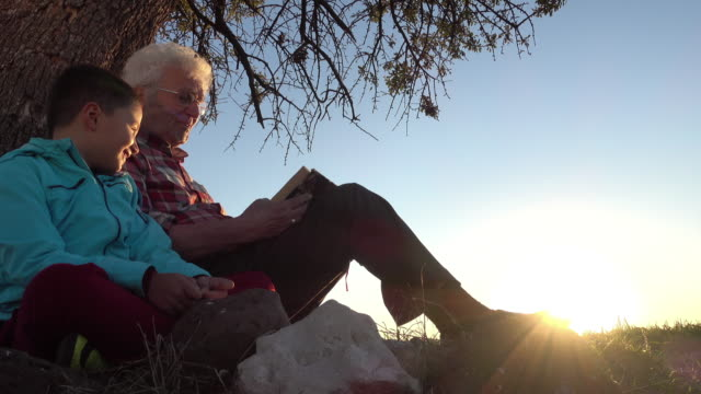 Grandfather reading story book with happy grandson