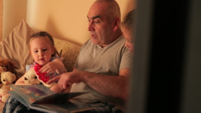 stockvideo's en b-roll-footage met grootvader lezing met zijn kleindochters - prentenboek