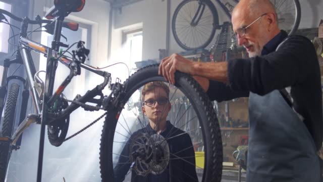 stockvideo's en b-roll-footage met slo mo grootvader het verwijderen van de buitenste band van de fiets bij het onderwijzen van zijn kleinzoon hoe een lekke band te herstellen - piercen