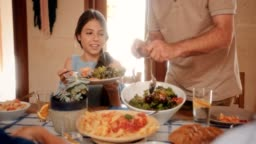 Grandfather serving granddaughter fresh Mediterranean salad at family lunch