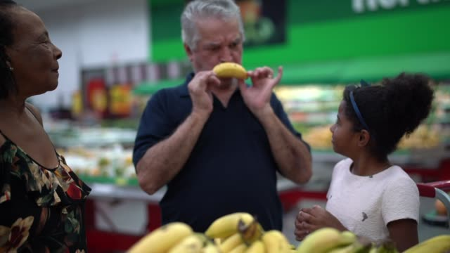 grandfather showing banana smiley face to his granddaughter at supermarket - senior couple stock videos & royalty-free footage