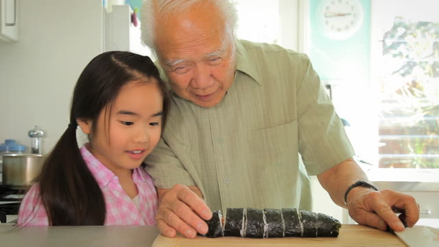 MS Grandfather showing granddaughter (8-9) how to cut roll of sushi / Los Angeles, California, USA