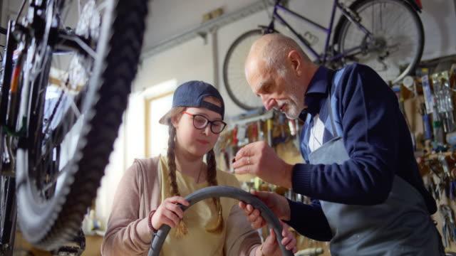 stockvideo's en b-roll-footage met slo mo grootvader toont zijn kleindochter hoe een patch plaats op de punctie van de binnenste buis van de fiets - part of a series