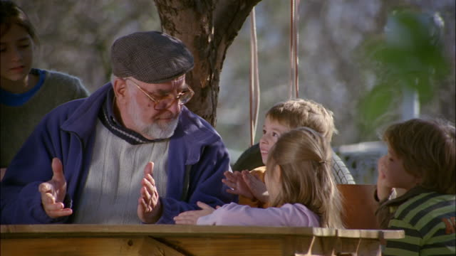 vidéos et rushes de a grandfather sits under a tree telling a story to his grandchildren. - histoire
