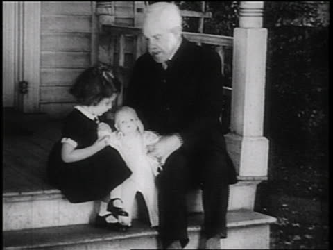b/w 1936 grandfather + small girl playing with doll on porch steps of house / documentary - ドール点の映像素材/bロール