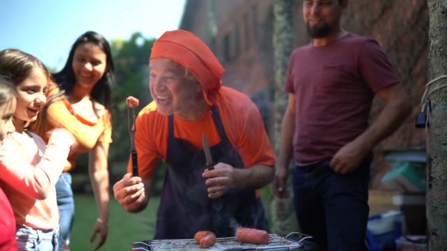 grandfather smeling a slice of meat ahd giving to granddaughter during a barbecue - barbecue stock videos & royalty-free footage