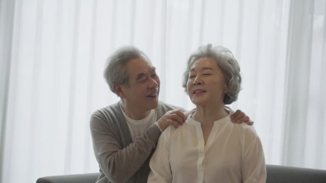 vídeos y material grabado en eventos de stock de a grandfather smiles while massaging grandmother's shoulders and a grandmother who likes it - massage room
