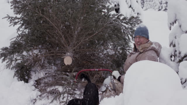 Grandfather smiling at grandson after cutting Christmas tree in snow in USA.
