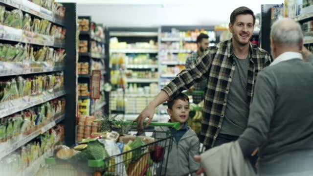 vídeos y material grabado en eventos de stock de abuelo, hijo y nieto en supermercado - carrito de la compra