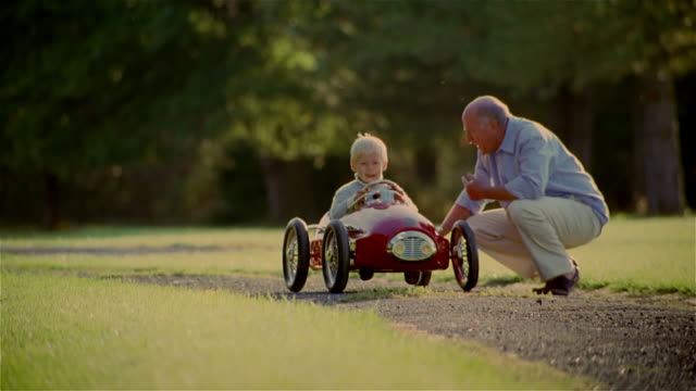stockvideo's en b-roll-footage met grandfather squatting next to young boy sitting in toy car / pushing grandson in toy car along gravel path and running behind - kleinzoon