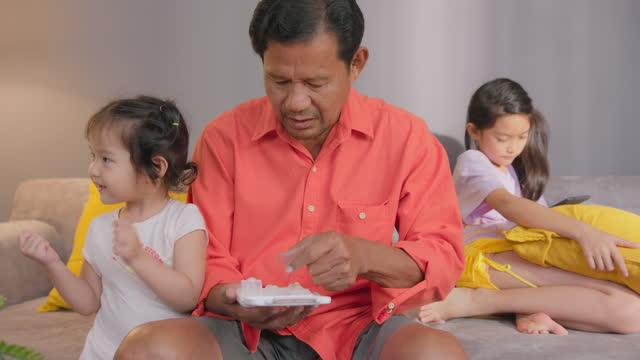 祖父は自宅で孫と一緒に薬やピルを飲んでいます。 - サプリメント点の映像素材/bロール