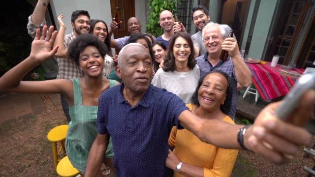バーベキュー パーティーで友人/家族の selfie を取る祖父 - バーベキューパーティー点の映像素材/bロール