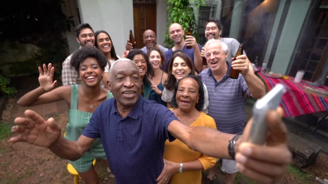 grandfather taking a selfie of friends/family at barbecue party - family reunion stock videos and b-roll footage