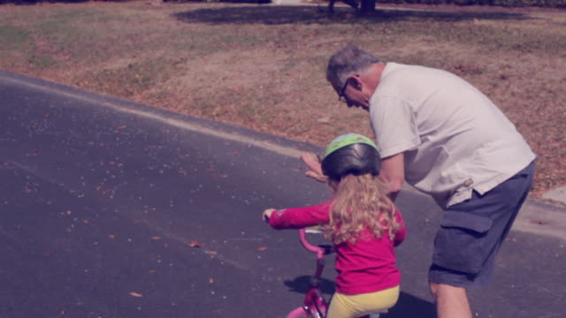 A grandfather teaches a young girl how to ride her bike for the first time