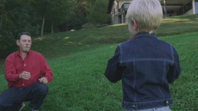 stockvideo's en b-roll-footage met a grandfather teaches his grandson how to hold, throw, and catch a football. - kleinzoon