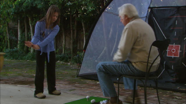 CU, ZO, MS, Grandfather teaching granddaughter (10-11) playing golf in backyard, Los Angeles, California, USA