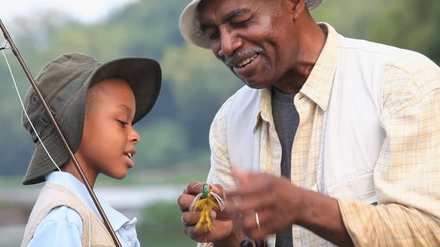 cu pan  grandfather teaching grandson (8-9) about fly fishing / richmond, virginia, usa - hobby video stock e b–roll
