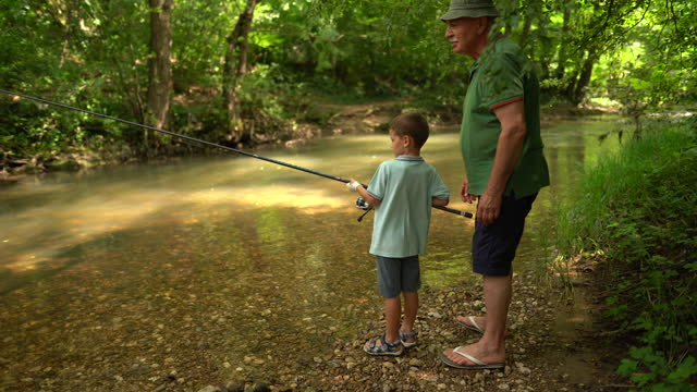 grandfather teaching grandson how to fish - enjoyment stock videos & royalty-free footage