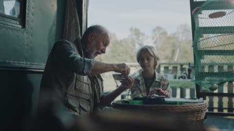 großvater lehrt enkel, wie man fischköder macht - zeigen stock-videos und b-roll-filmmaterial