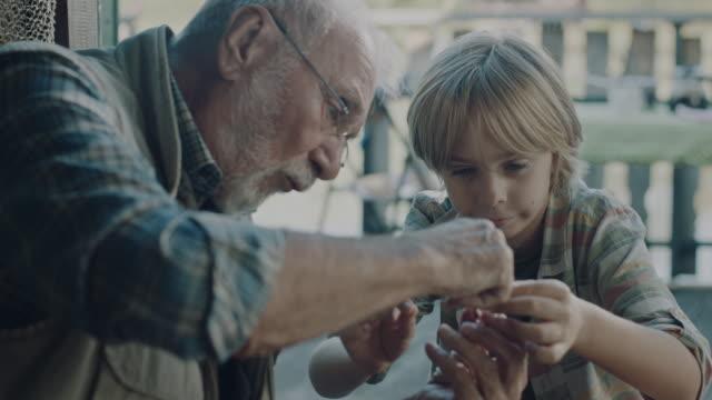 großvater lehrt enkel, wie man fischköder macht - enkel stock-videos und b-roll-filmmaterial
